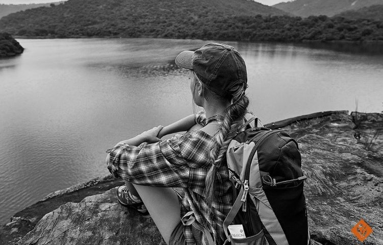 Black and white image of woman sitting on a rock, staring at the lake and mountains